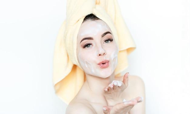 Красивая молодая женщина наслаждается рутиной ухода за кожей лица.