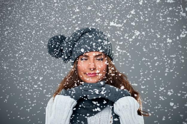 La bella giovane donna gode della prima neve