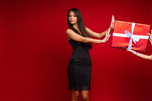 Beautiful young woman in evening black dress refuse from gift on red studio background with copy space for advertising