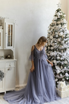 Beautiful young woman in the evening dress stands in a room decorated for christmas