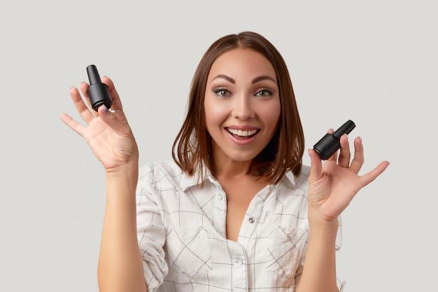 Красивая молодая женщина взволнована и смотрит в камеру, держа бутылки портрета красоты лака для ногтей ...