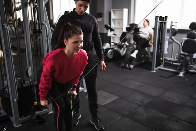 クロスオーバージムマシンで運動する美しい若い女性
