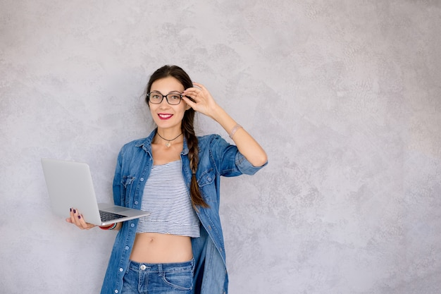 Beautiful young woman in eyeglasses standing with a laptop in her hands