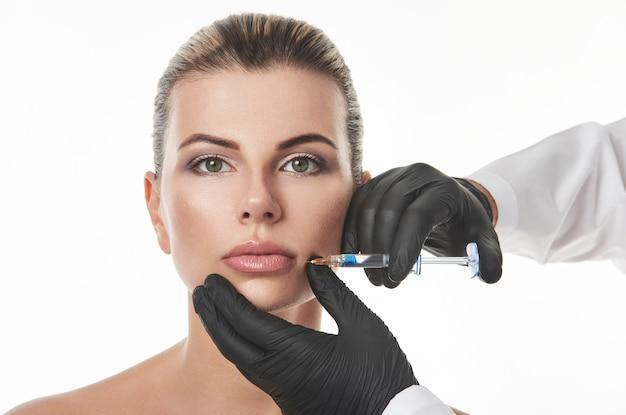 주사기와 입술에 주입을 만드는 검은 장갑에 아름 다운 젊은 여자 얼굴과 성형 외과 의사의 손