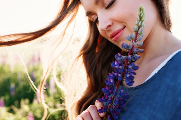 Beautiful young woman face portrait in lupine field, holding flower near cheek.