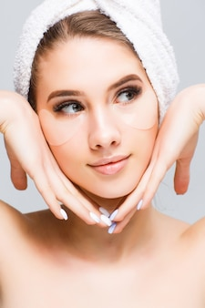 Beautiful young woman face with white towel on her head