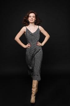 フルショットを歩いて笑顔のエレガントなドレスを示す美しい若い女性のファッションモデル。黒のスタジオの背景で隔離のポーズをとってフェミニンな美しさの服の愛らしい女性