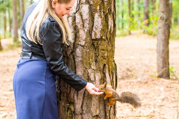 Красивая молодая женщина кормит белку в осеннем парке