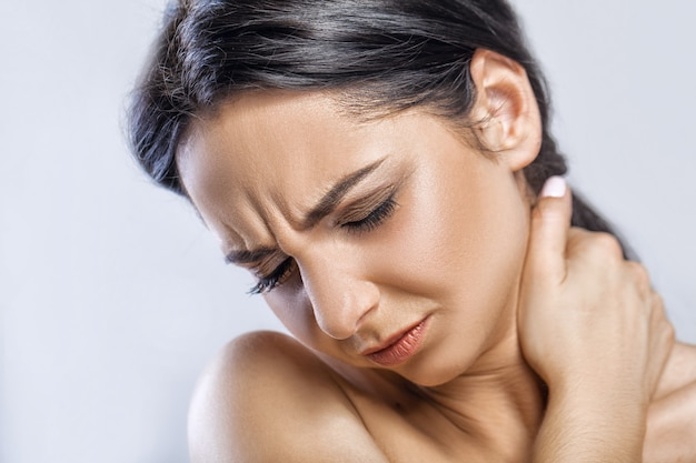 Beautiful young woman feeling pain in the neck
