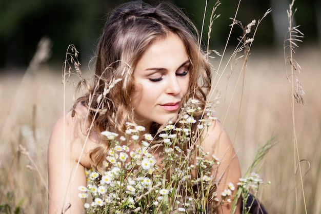 Beautiful young woman in a field among camomiles enjoys nature.