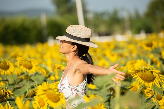 Beautiful young woman in a field of sunflowers in a white dress. travel on the weekend concept. portrait of authentic woman in straw hat . outdoors on the sunflower field.