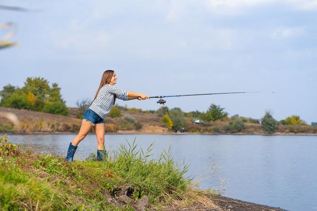 美しい若い女性は湖で魚します。