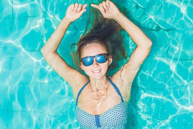 상위 뷰를 편안 하 게 수영장에 떠있는 아름 다운 젊은 여자