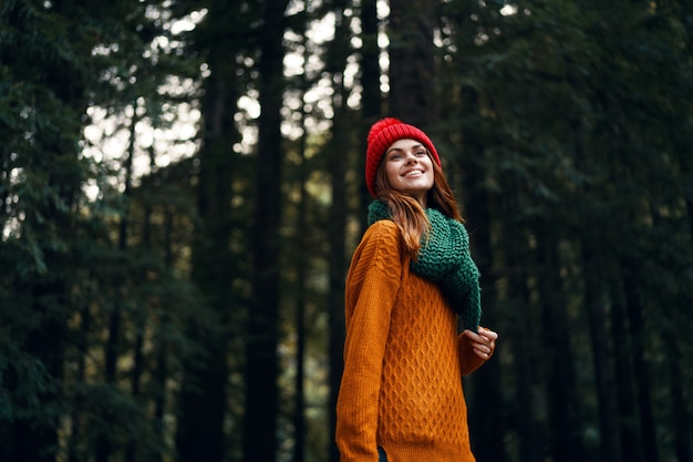 Beautiful young woman in the forest in bright clothes, a red hat, an orange sweater, in a green scarf travels, hiking in nature in the forest