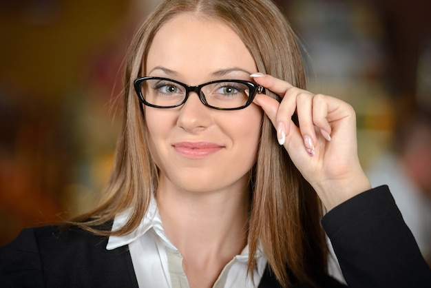 Beautiful young woman in formalwear adjusting glasses.