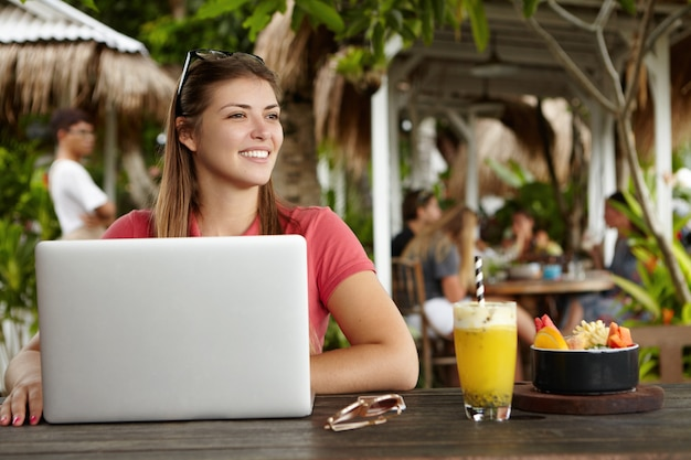 Beautiful young woman freelancer dressed casually using generic laptop computer for remote work, having rest at outdoor restaurant
