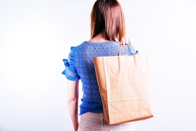 Beautiful young woman from behind with a paper bag behind her back. sustainable shopping concept. plastic free