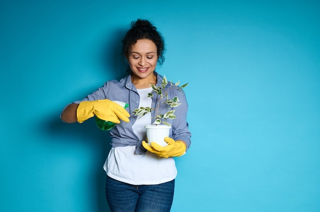 Beautiful young woman gardener in yellow gloves watering a transplanted small tree.