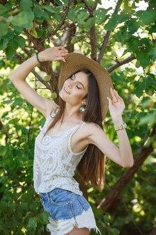 夏の自然の中で外でガーデニング美しい若い女性。証書と夏の離れ家、緑豊かな庭園と自由の概念
