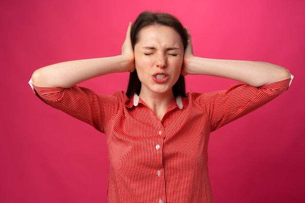 Красивая молодая женщина жестикулирует, что не хочет слышать, и держится руками за уши на розовой спине ...
