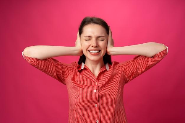 Красивая молодая женщина делает жесты, которые не хочет слышать, и держит руки за уши на розовой спине ...