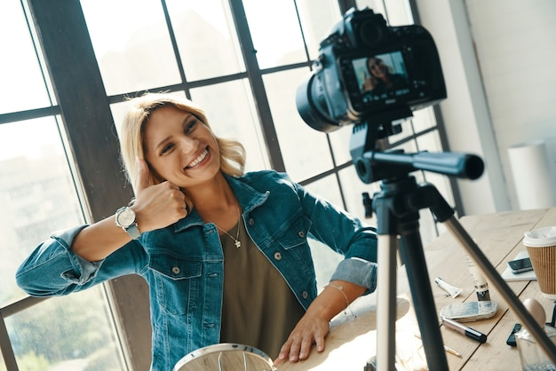 아름 다운 젊은 여자 몸짓과 디지털 카메라 앞에서 작업하는 동안 웃 고