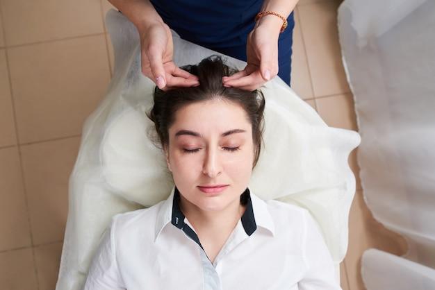 Красивая молодая женщина получает лечение лица и головы в салоне красоты