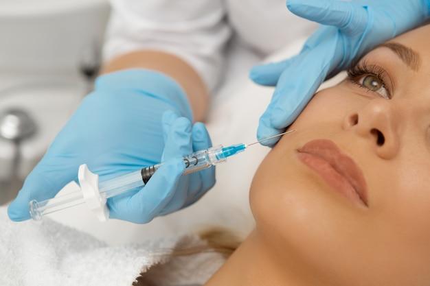 美しい若い女性は彼女の顔に美容注射を取得