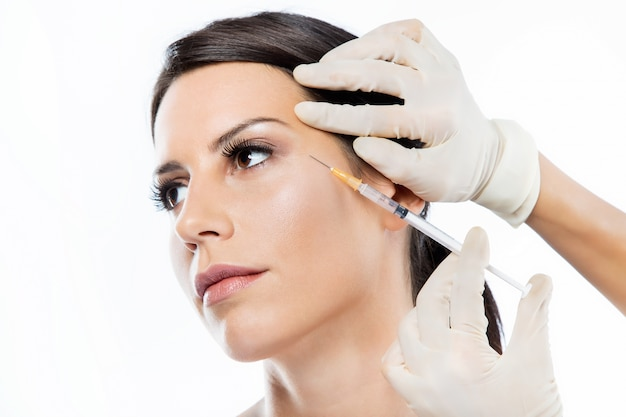 Beautiful young woman getting botox cosmetic injection in her face.
