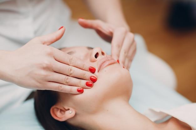 Красивая молодая женщина, получая массаж лица в спа-салоне красоты.