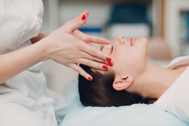 뷰티 스파 살롱에서 얼굴 치료 마사지를 받고 아름 다운 젊은 여자.