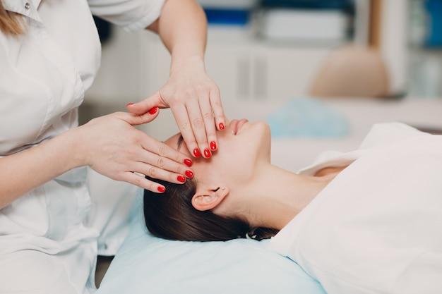 뷰티 스파 살롱에서 얼굴 치료 마사지를 받고 있는 아름다운 젊은 여성.
