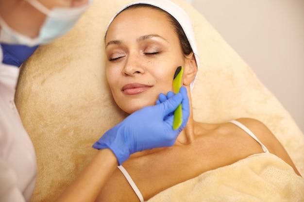 Красивая молодая женщина получает уход за лицом косметолог в спа-салоне