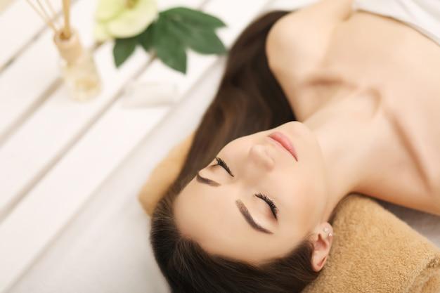 Красивая молодая женщина, получающая массаж лица, лежа на диване