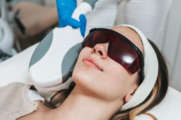 Красивая молодая женщина, получая косметологическую процедуру удаления волос в косметической спа-клинике красоты.