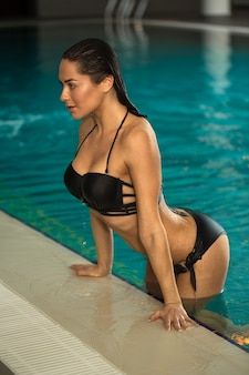 Beautiful young woman getting out from the pool at spa center