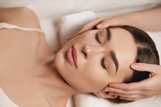 Beautiful young woman getting spa face massage treatment at beauty spa salon