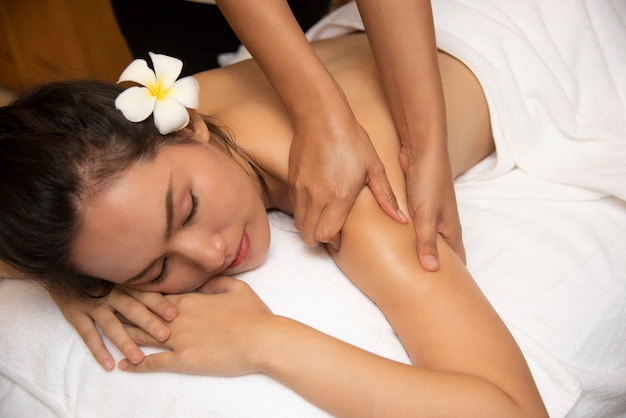 Beautiful young woman getting spa massage salon and white flower on her ear.