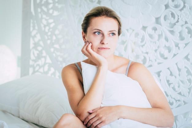 Красивая молодая женщина девушка в спальне утром дома, просыпаясь и глядя
