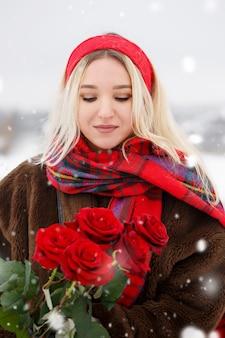 아름 다운 젊은 여자는 발렌타인 데이에 빨간 장미 꽃다발을 제공합니다