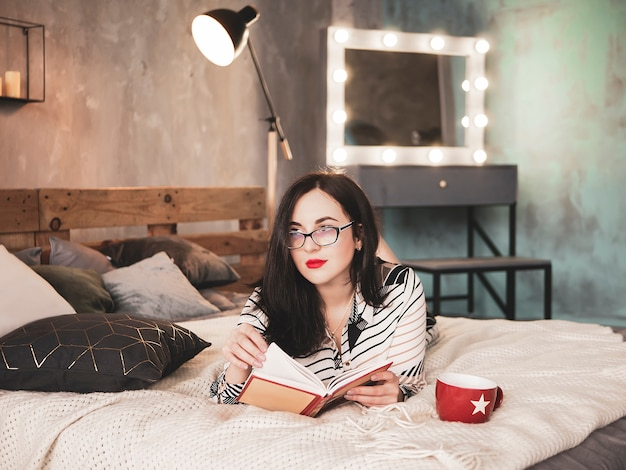 Beautiful young woman in glasses with cup of tea reading book while lying on bed. rest, comfort, leisure and people concept