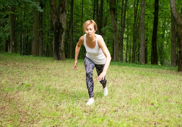아름 다운 젊은 여자는 자연 공원에서 스포츠에 들어갑니다. 여자는 운동복에서 피트니스에 종사하고 있습니다. 충전 중. 스트레칭.