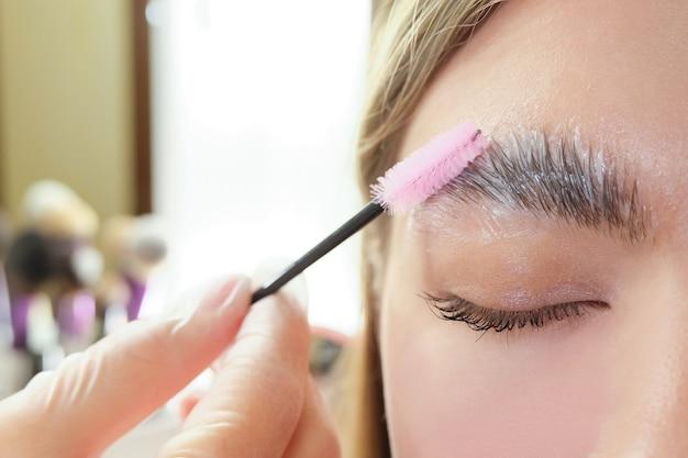 美しい若い女性が美容院で眉毛の矯正を受けました