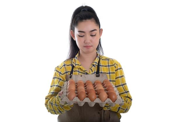 白い背景の上の列に並んでいる鶏卵と卵のカートンを持っている美しい若い女性の手