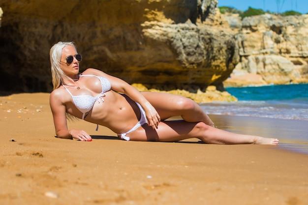 白いビキニと赤い縞模様のビーチでいくつかの岩の近くで幸せに日光浴をしている美しい若い女性