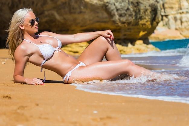 Красивая молодая женщина счастливо загорает возле скал на пляже в белом бикини и красных полосах