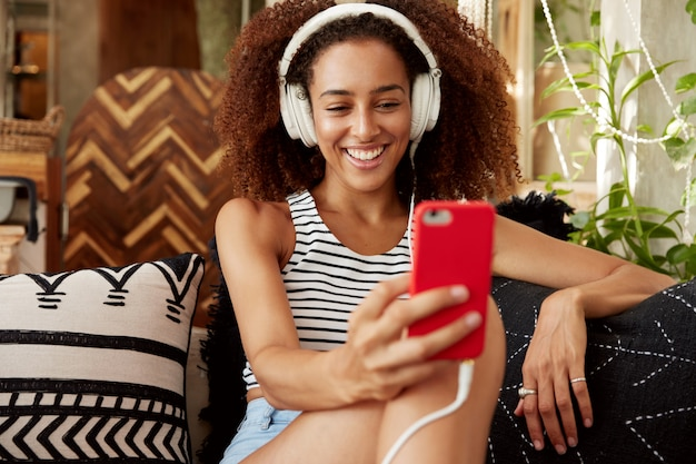 Beautiful young woman has afro hairstyle, makes video call via smart phone and headphones, speaks with friend online while sits at comfortable sofa with cushions.