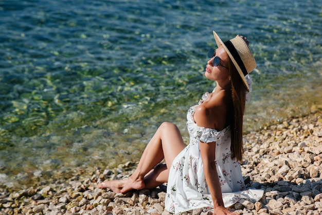 A beautiful young woman in a hat, glasses and a light dress is sitting on the ocean shore against the background of huge rocks on a sunny day. tourism and tourist trips.