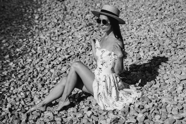 A beautiful young woman in a hat, glasses and a light dress is sitting with her back to the ocean against the background of huge rocks on a sunny day. tourism and tourist trips. black and white.