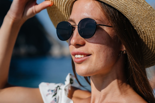 A beautiful young woman in a hat, glasses and a light dress is walking along the ocean shore against the background of huge rocks on a sunny day. tourism and tourist trips.